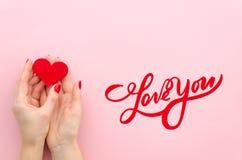AIMEZ-VOUS lettrage de main la femme Hans tient le coeur rouge sur un fond rose la vue que supérieure étendent à plat à la mode photo stock