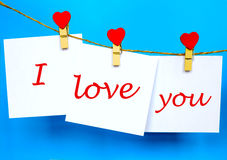 Aimez-vous texte sur des autocollants accrochant sur des goupilles de forme de coeur Images stock