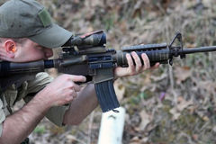 Aiming Tacticle Rifle. Man aims a precision rifle at an off-camera target Royalty Free Stock Images