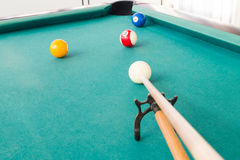 Aiming ball using extender stick during snooker billards game. On green table Royalty Free Stock Photography