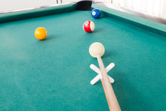 Aiming ball using extender stick during snooker billards game. On green table Royalty Free Stock Image