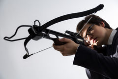 Aiming crossbow. Businessman aiming with crossbow on light background Royalty Free Stock Photography