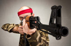 Aiming funny soldier. Portrait of funny soldier aiming with machine gun stock photo
