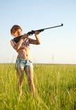 Aiming girl. Young girl aiming pneumatic air rifle outdoor stock photos