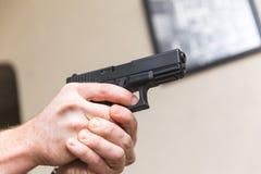 Aiming Gun Inside Home. Male hands hold a gun aimed inside a house. Gun is a black 9mm pistol Stock Image