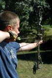 Aiming his arrow. Young man practices his archery with his compound hunting bow Stock Images
