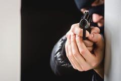 Aiming murderer with a gun Stock Photos