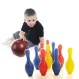 Aiming for the Pins. An adorable preschooler aiming a heavy bowling ball at colorful plastic pins. Focus on the pins. On a white background royalty free stock photo