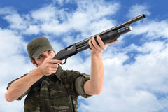 Aiming And Shooting With Rifle. A man (soldier, hunter, guerrilla, etc.) wearing a camouflage clothing is aiming with his pump action shotgun and cloudy sky Royalty Free Stock Image