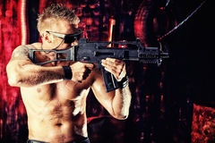 Aiming soldier. Portrait of a handsome muscular soldier man holding a machine gun. Grunge background Stock Photos