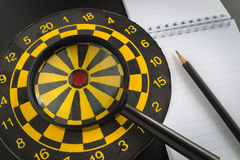 Aiming target analysis concept with magnifying glass on dart boa Stock Images