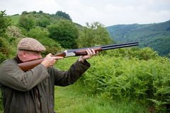 West country farmer with a shotgun. Aiming and about to shoot a shotgun stock photo