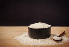 Ainda arroz branco da vida na bacia preta no fundo de madeira Imagem de Stock