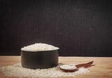 Ainda arroz branco da vida na bacia preta no fundo de madeira Fotos de Stock