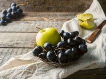Ainda as uvas e as maçãs da vida em uma placa do vintage na cópia de madeira rústica do fundo espaçam o foco seletivo Foto de Stock Royalty Free