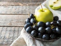 Ainda as uvas e as maçãs da vida em uma placa do vintage na cópia de madeira rústica do fundo espaçam o foco seletivo Imagens de Stock