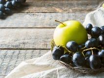 Ainda as uvas e as maçãs da vida em uma placa do vintage na cópia de madeira rústica do fundo espaçam o foco seletivo Foto de Stock