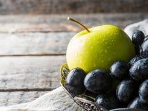 Ainda as uvas e as maçãs da vida em uma placa do vintage na cópia de madeira rústica do fundo espaçam o foco seletivo Imagem de Stock