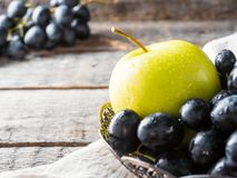 Ainda as uvas e as maçãs da vida em uma placa do vintage na cópia de madeira rústica do fundo espaçam o foco seletivo Imagem de Stock Royalty Free