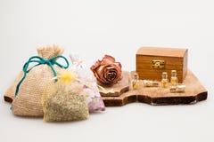 Ainda a composição da vida com a alfazema, secada aumentou, a caixa de madeira e vidros pequenos com papel dourado Foto de Stock Royalty Free