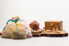Ainda a composição da vida com a alfazema, secada aumentou, a caixa de madeira e vidros pequenos com papel dourado Fotos de Stock