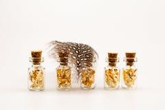 Ainda composição da vida com as garrafas de vidro pequenas com papel dourado Fotos de Stock