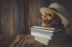Ainda crânio da vida Weave e livros da máquina do tampão no fundo de madeira Imagem de Stock