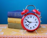 Ainda despertador retro vermelho da vida e três livros Fotos de Stock