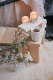 Ainda detalhes da vida de interior: roupa feita malha em um assoalho de madeira do vintage, no copo do chá e no livro Fotografia de Stock Royalty Free