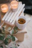 Ainda detalhes da vida de interior: roupa feita malha em um assoalho de madeira do vintage, no copo do chá e no livro Imagem de Stock