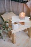 Ainda detalhes da vida de interior: roupa feita malha em um assoalho de madeira do vintage, no copo do chá e no livro Fotos de Stock