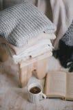 Ainda detalhes da vida de interior: roupa feita malha em um assoalho de madeira do vintage, no copo do chá e no livro Fotografia de Stock