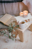 Ainda detalhes da vida de interior: roupa feita malha em um assoalho de madeira do vintage, no copo do chá e no livro Fotos de Stock Royalty Free