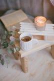 Ainda detalhes da vida de interior: roupa feita malha em um assoalho de madeira do vintage, no copo do chá e no livro Foto de Stock Royalty Free