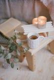 Ainda detalhes da vida de interior: roupa feita malha em um assoalho de madeira do vintage, no copo do chá e no livro Imagens de Stock