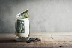 ainda dinheiro da vida no vidro na tabela de madeira com o espaço da cópia lido Fotos de Stock Royalty Free