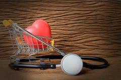 Ainda a fotografia da pintura da vida com estetoscópio e o coração vermelho dão forma nos mini carrinhos de compras enchidos com  Imagens de Stock