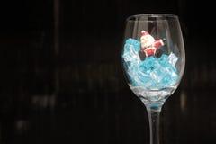 Ainda fotografia da vida com Santa Claus em um vidro do vinho com gelo na noite com fundo escuro, Fotos de Stock