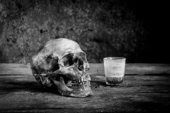 Ainda fotografia preto e branco da vida com os crânios humanos na madeira Imagem de Stock