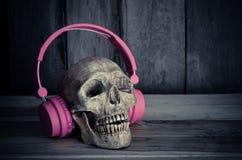 Ainda modelo humano do crânio da vida com os fones de ouvido cor-de-rosa no fundo de madeira Imagens de Stock Royalty Free