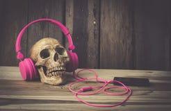 Ainda modelo humano do crânio da vida com os fones de ouvido cor-de-rosa no fundo de madeira Fotografia de Stock Royalty Free