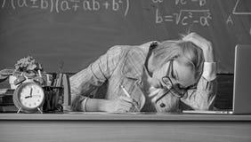 ainda trabalhando Trabalho para além do dia escolar real A cara cansado do professor mantém-se trabalhar após classes Professor o imagens de stock