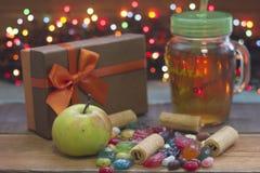 Ainda uma vida festiva com uma maçã, um giftbox marrom, um copo de vidro do chá com um tampão, uns doces e umas cookies, luzes fe Imagens de Stock Royalty Free