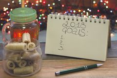 Ainda uma vida festiva com um copo claro de vidro do chá com um tampão, inscrição de 2018 objetivos, uma bacia de cookies, luzes  fotos de stock royalty free