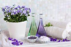 Ainda vida, óleo da massagem em umas garrafas, com flores, em toalhas de uma bandeja e em ervas nos termas Fotografia de Stock Royalty Free