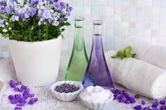Ainda vida, óleo da massagem em umas garrafas, com flores, em toalhas de uma bandeja e em ervas nos termas Imagens de Stock Royalty Free