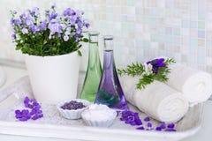 Ainda vida, óleo da massagem em umas garrafas, com flores, em toalhas de uma bandeja e em ervas nos termas Imagem de Stock