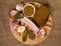 Ainda vida: Aperitivo do bacon na placa de madeira redonda Imagem de Stock