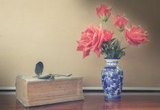 Ainda a vida artificial aumentou no vaso com relógio e livro Fotografia de Stock Royalty Free