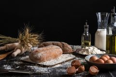 Ainda vida bonita com tipos diferentes do pão, da grão, da farinha no peso, das orelhas do trigo, do jarro do leite e dos ovos Fotos de Stock